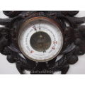 an antique carved wooden Black Forest barometer