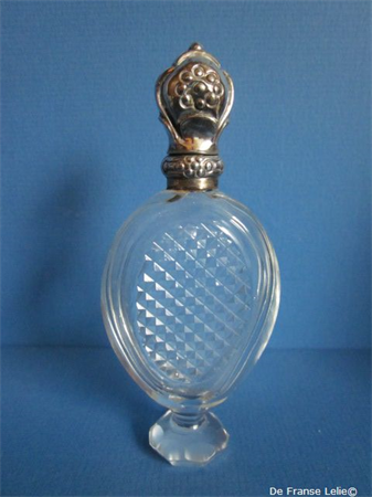 an antique crystal perfume bottle with silver top