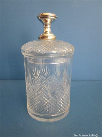 an antique crystal sugar pot with silver top