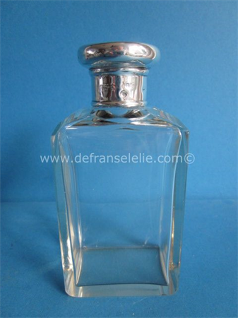an antique crystal scent bottle with silver top