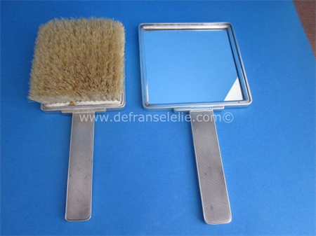 an antique silver mirror and brush