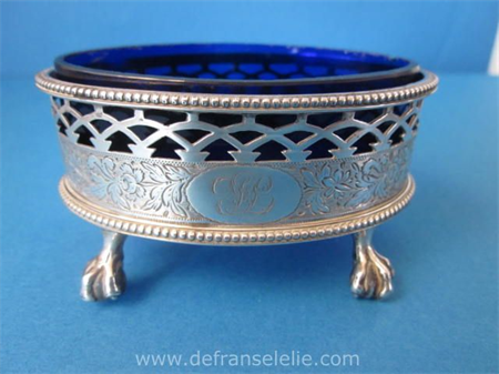 an antique sterling silver salt cellar with blue glass liner