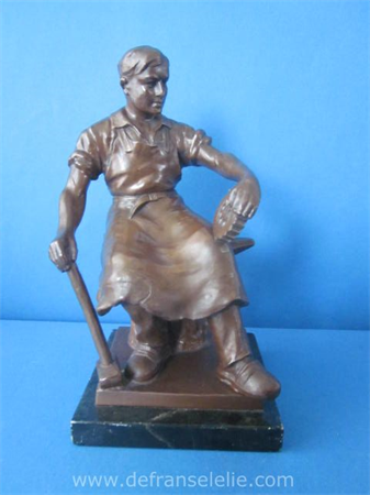 a vintage bronze figure of a blacksmith