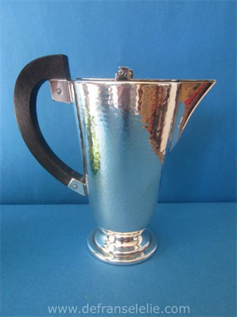 a silver plated hammered art deco jug with ebony handle