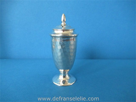 an antique sterling silver hammered pepper caster