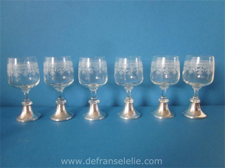 a set of six small wine glasses with silver stand