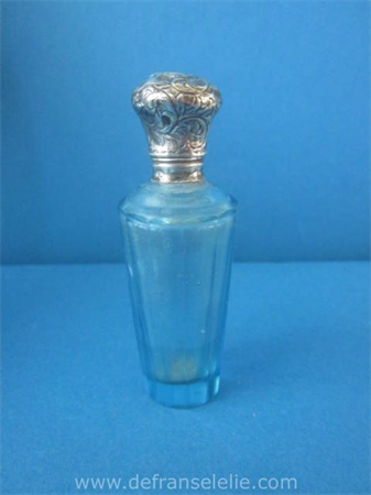 an antique French glass perfume bottle with silver top